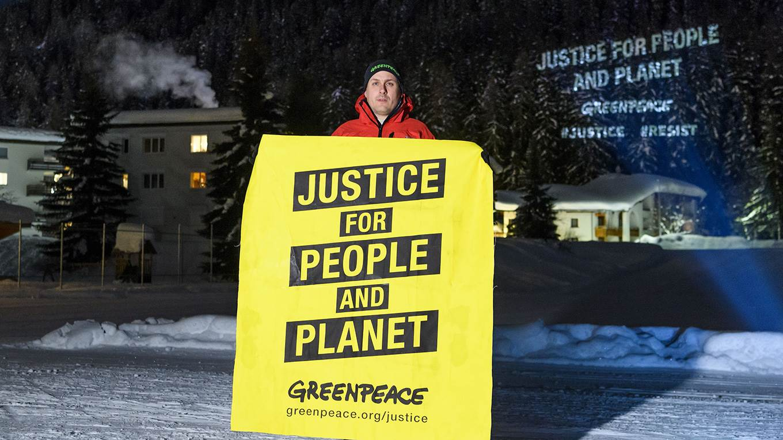 A Greenpeace activist holds a placard