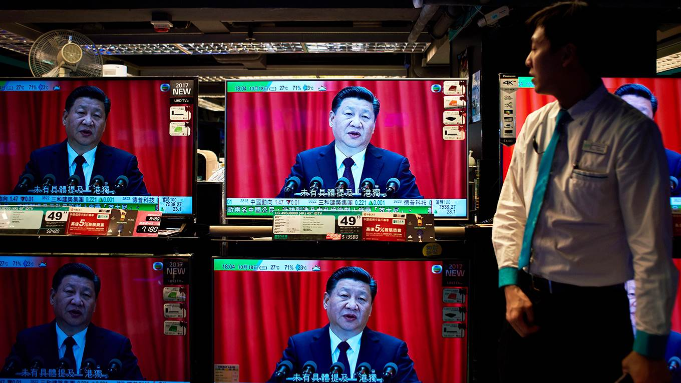 Television sets showing a news report on Xi Jinping's speech