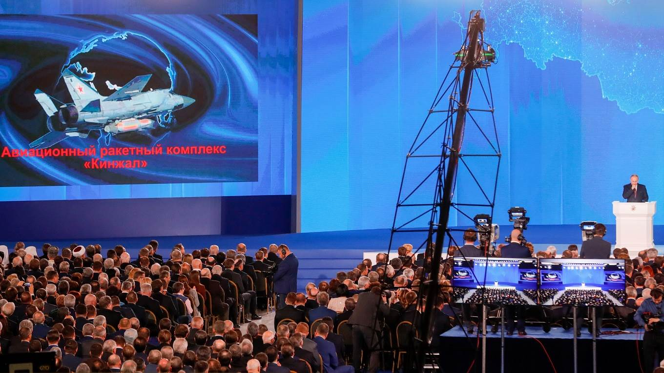 The video screen shows the Kinzhal shipborne surface-to-air missile system as Putin delivers an annual address to the Federal Assembly
