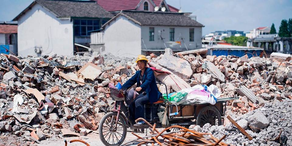 A migrant worker on her tricycle at the demolition site of the Jiuxing furniture market