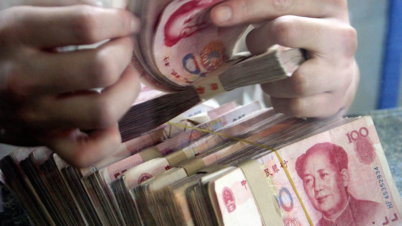 A bank teller counts Chinese currency 100 yuan (or Renminbi) notes