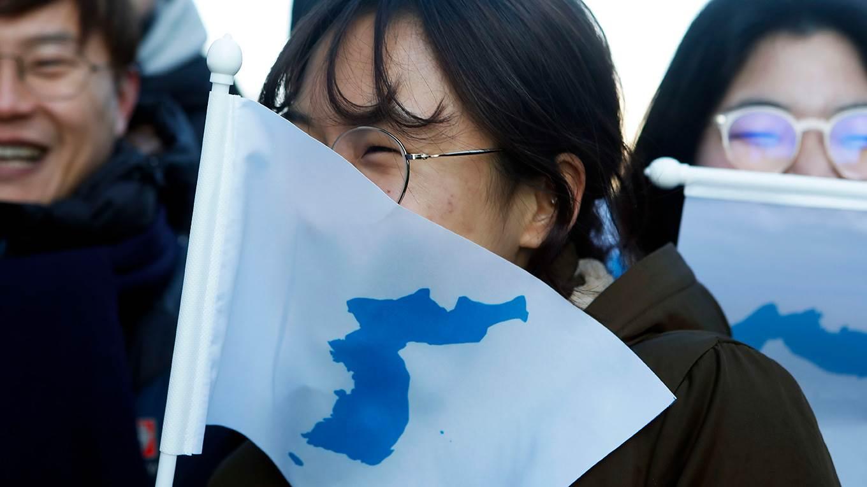 South Korean peace activists carry the Flag of Korean Peninsula