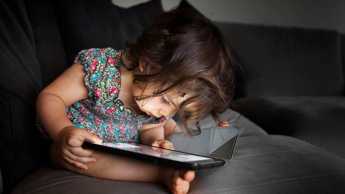 Toddler concentrated with a tablet