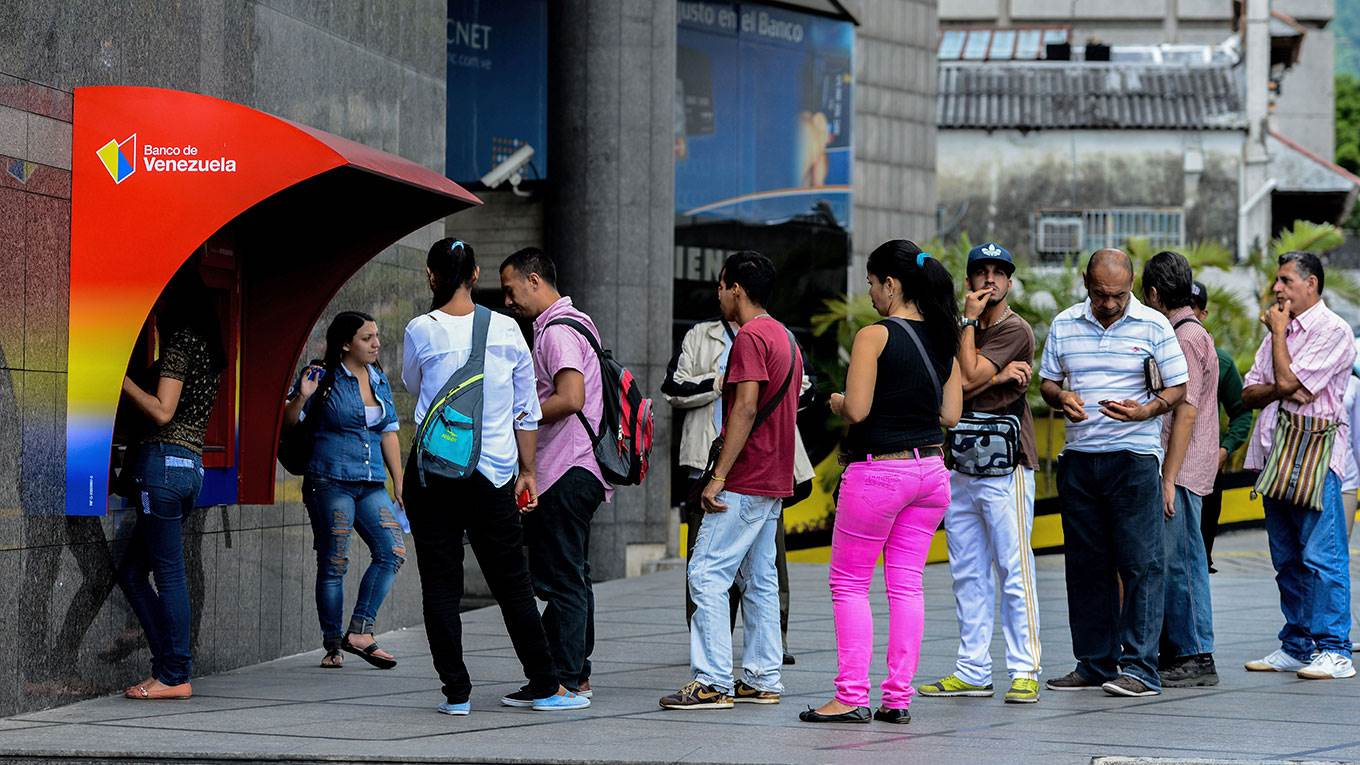People queue to withdraw money from an ATM in Caracas