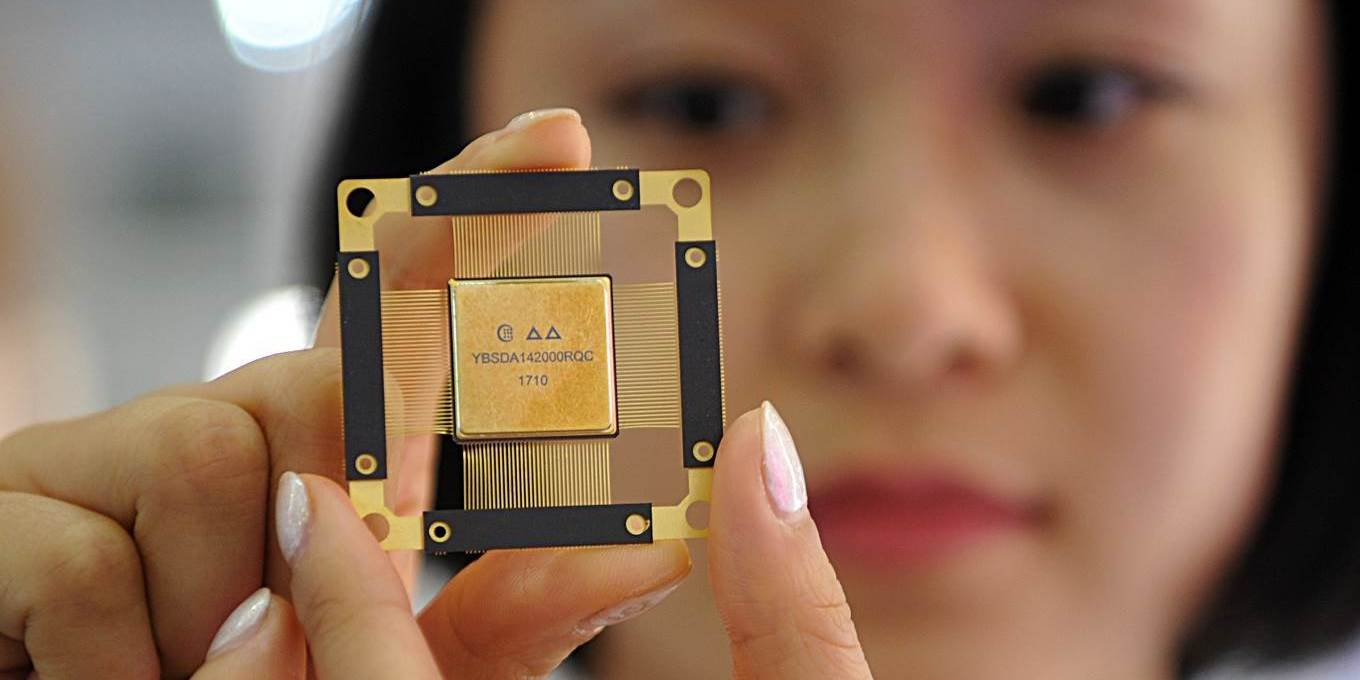 A worker presents a chip for fifth-generation (5G) mobile networks at China Electronics Technology Group