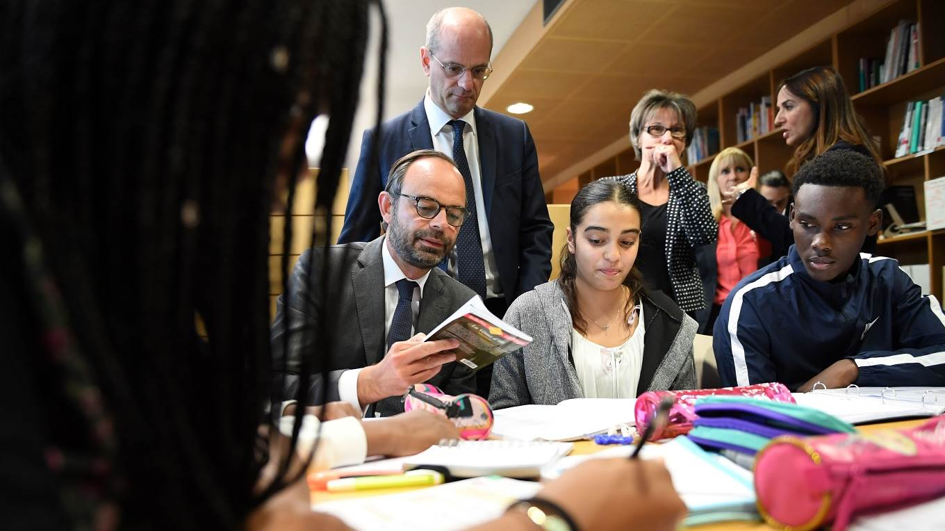 French Prime Minister Edouard Philippe speaks with pupils as he visits the Jean Perrin secondary school