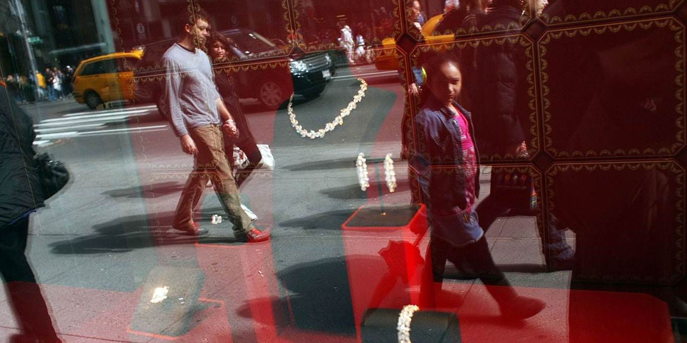 Pedestrians look at diamonds in a window display along 5th Avenue