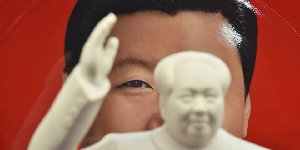 Chinese President Xi Jinping is seen behind a statue of late communist leader Mao Zedong