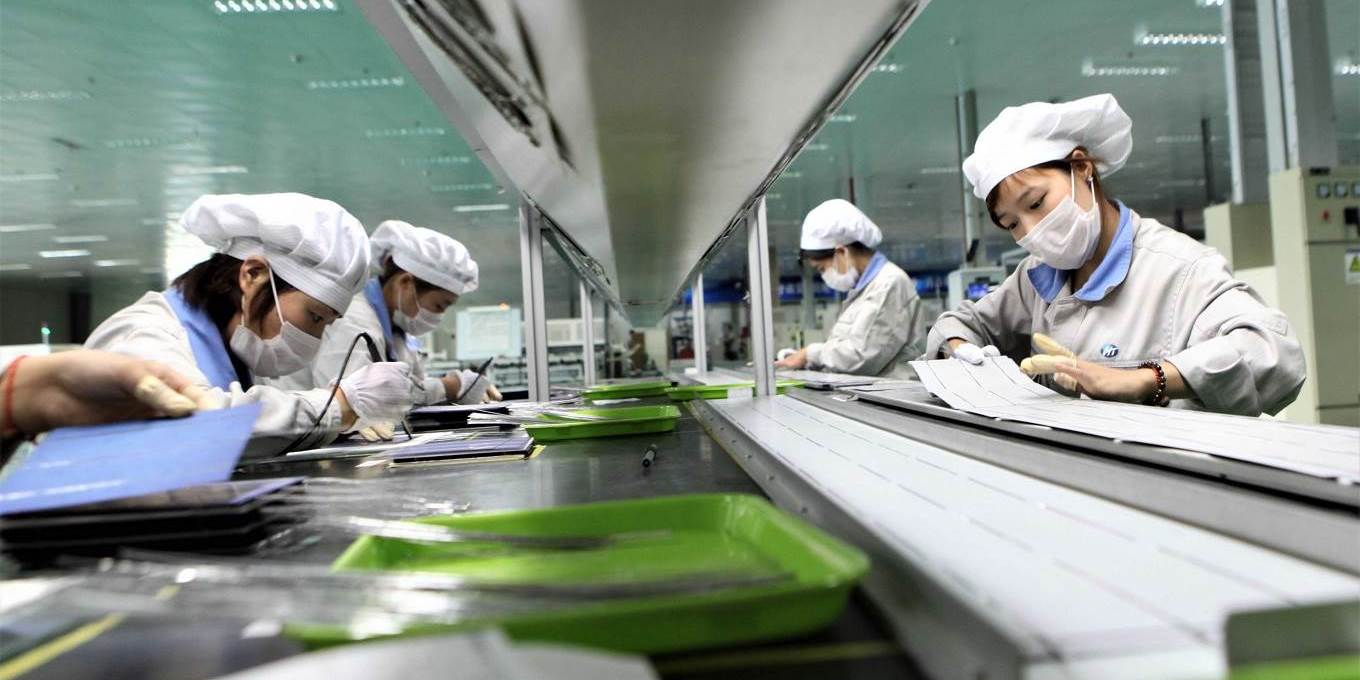 Employees work on a solar panel production line at Shenzhou New Energy Co