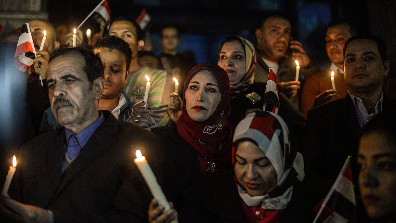 Egyptians hold candles at a vigil