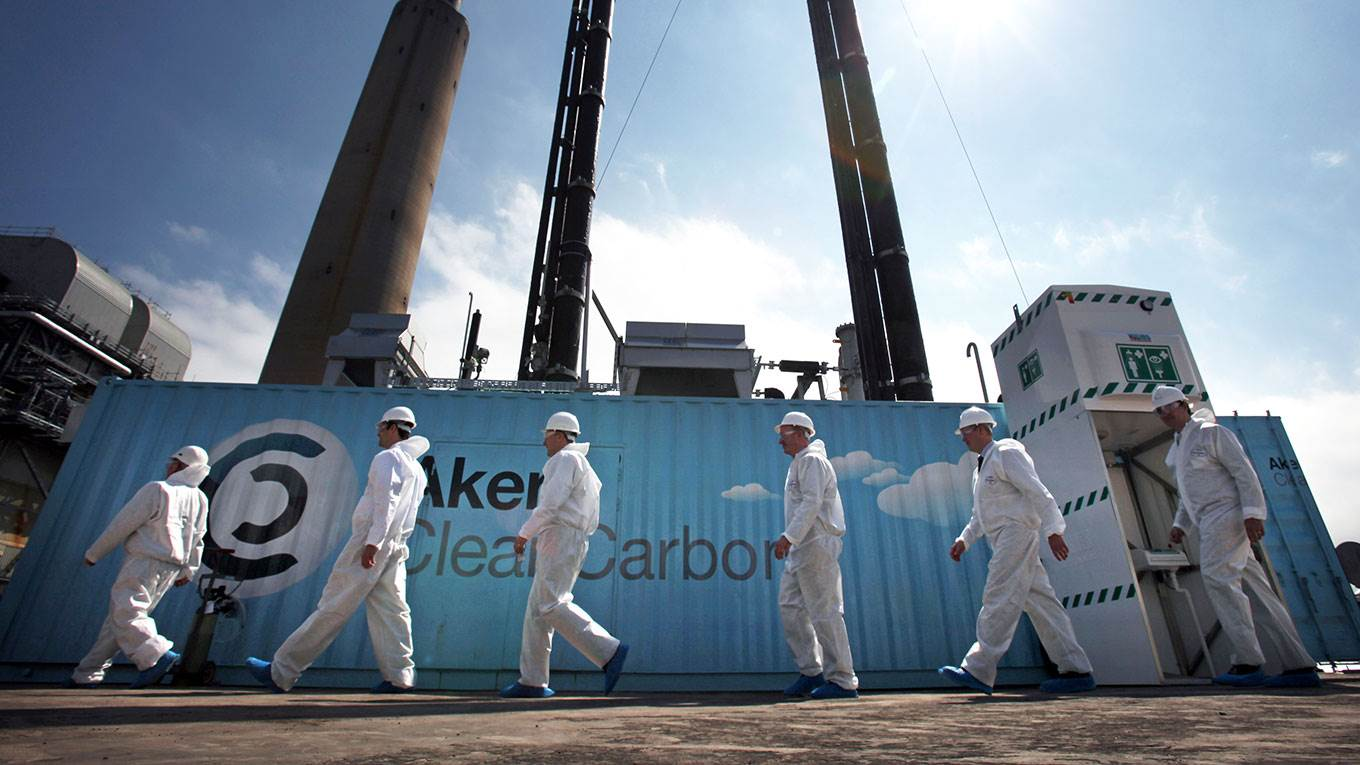 Scientists stand beside a new carbon capture test unit