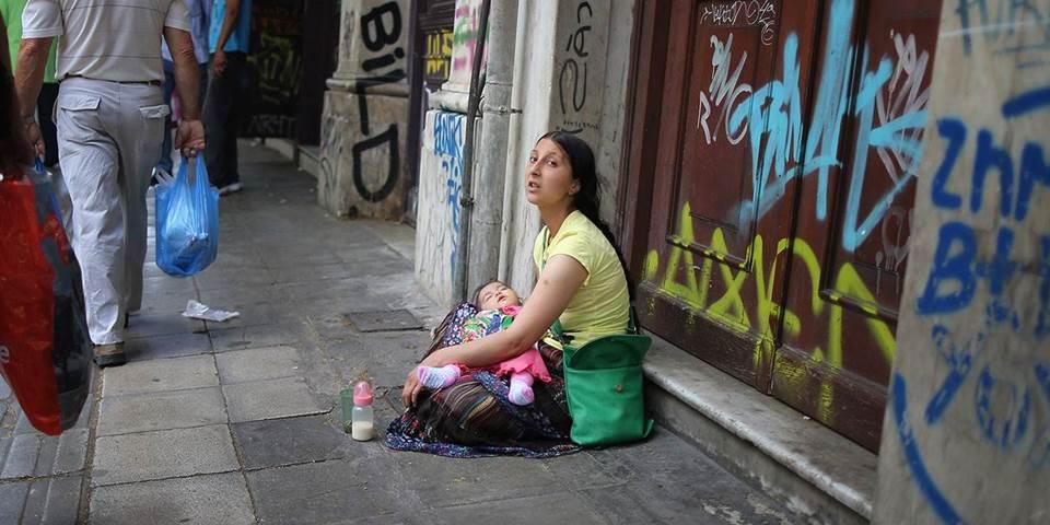 austerity woman sitting on street