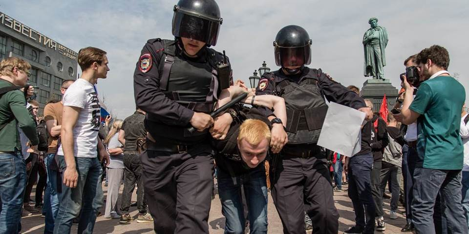 Russian Police forces seen arresting a protester during the demonstration