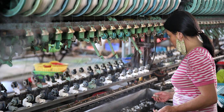 Woman working on silk spinning machine