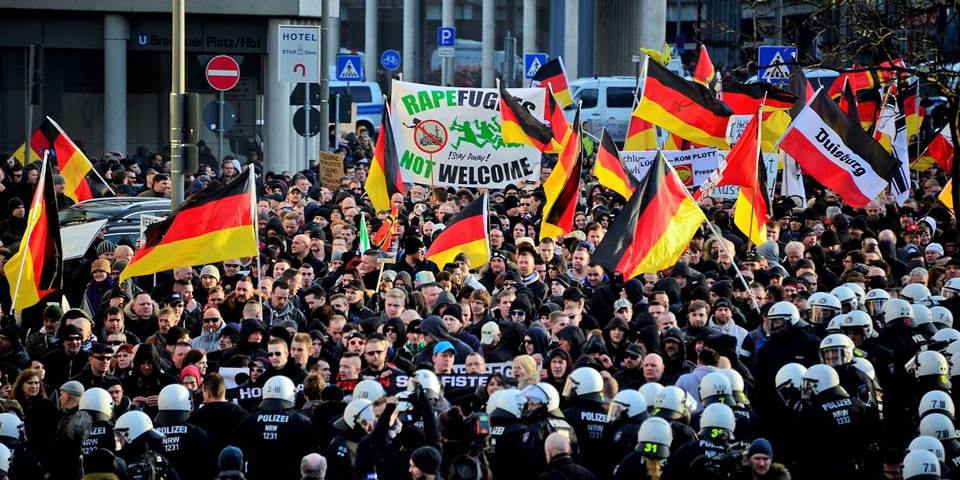 Protesters wave German flags, alongside a banner saying 'Rapefugees Not Welcome'