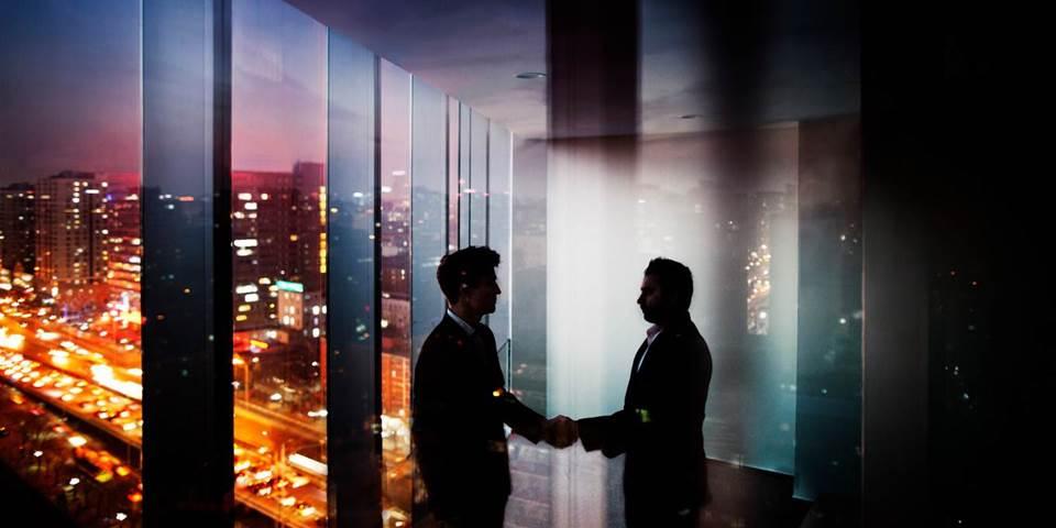 businessmen shake hands night