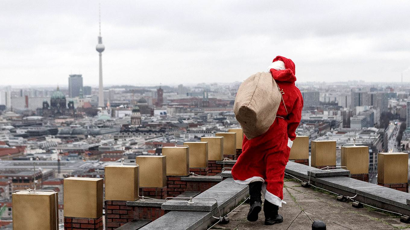 An actor dressed as Santa Claus pretends to retrieve a lost package