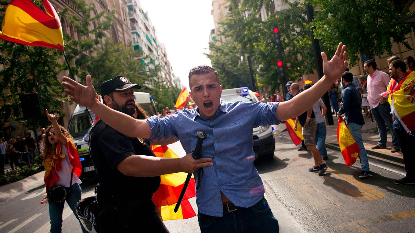 A Spanish policeman tries to avoid clashes between people holding Spanish flags