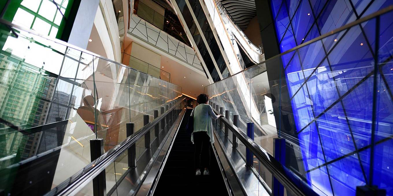 A woman uses an escalator in a shopping mall in Shanghai