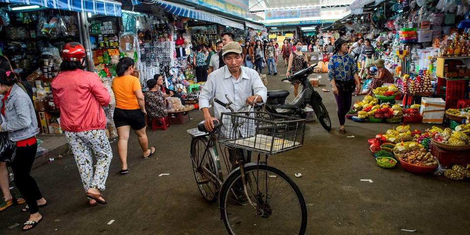 A man walks with his bicycle in the Con Market in the central Vietnamese city of Danang