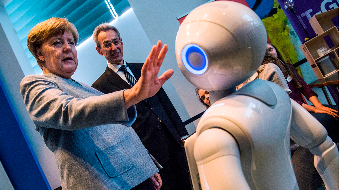 Angela Merkel gestures towards an interactive robot