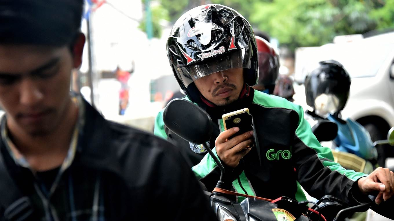 A GrabBike rider uses his mobile phone