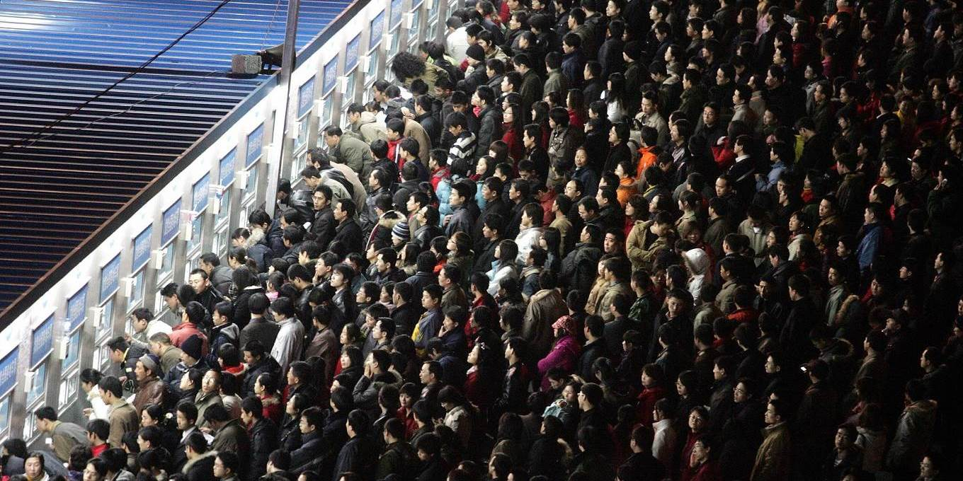 Thousands of Chinese travellers rush to buy their train tickets at the railway station in Beijing